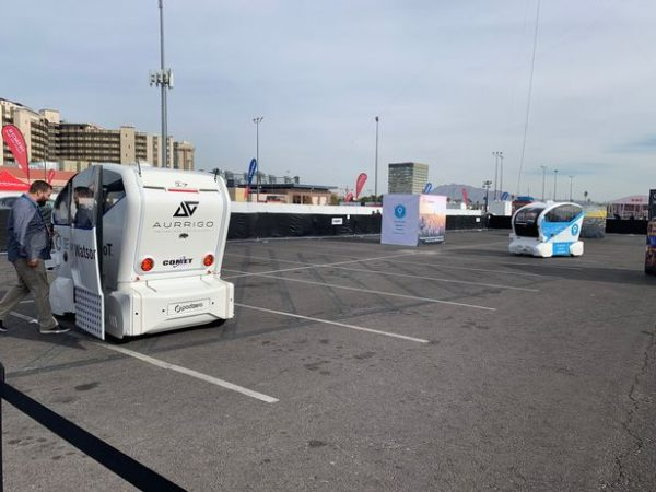 Two self-driving pods take guests for a ride in a car park at a UK show