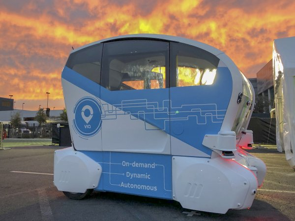 A self-driving pod photographed against a sunset background