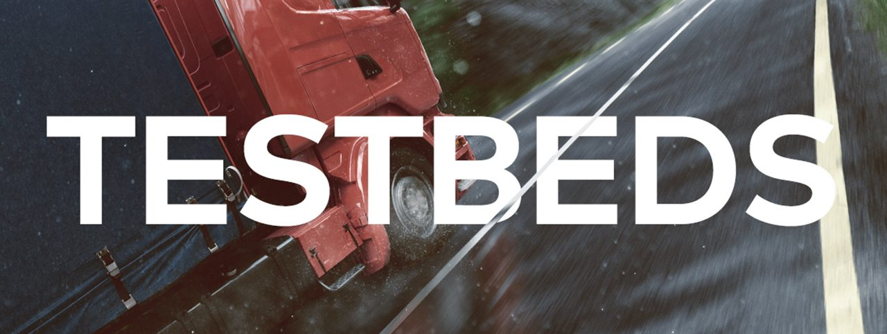 A truck drives on a road, the image is intersected by the word 'Testbeds'