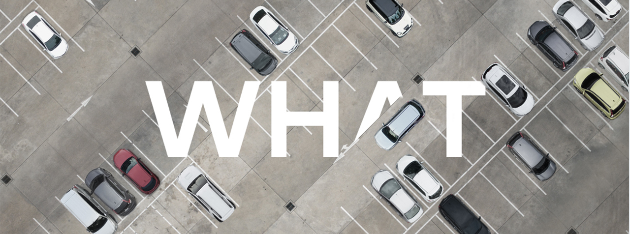 Cars parked in a car park from overhead, intersected by the word 'What'