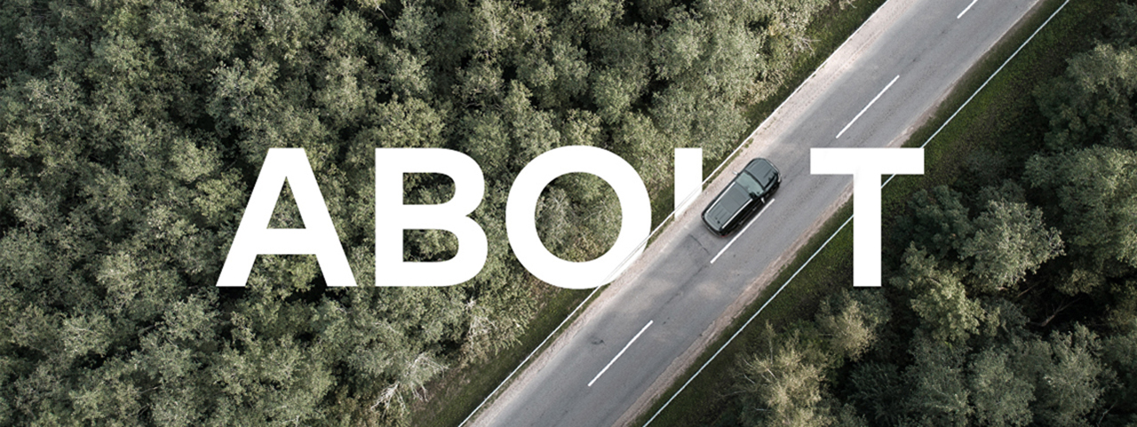 Trees and a road from above, the image intersected by the word 'About'