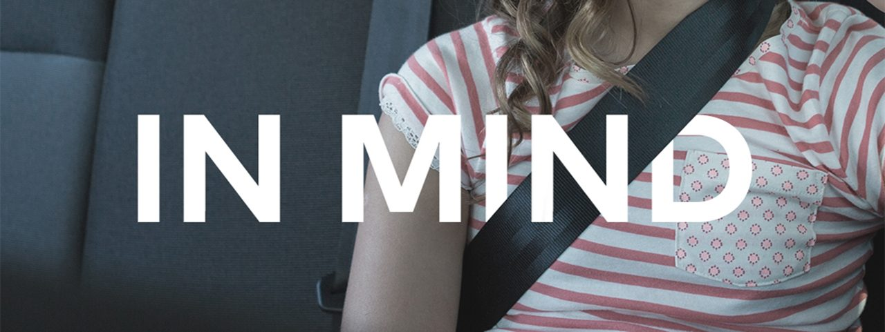 A young girl sits in a car with a seatbelt on, the image intersected with the words 'In mind'
