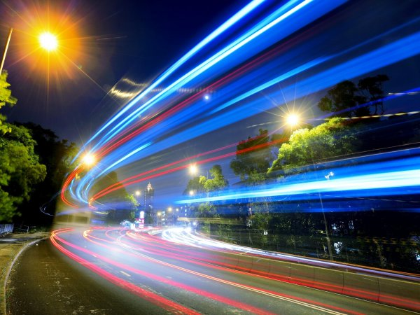 A road at night with a slow shutter speed displaying car lights speeding past